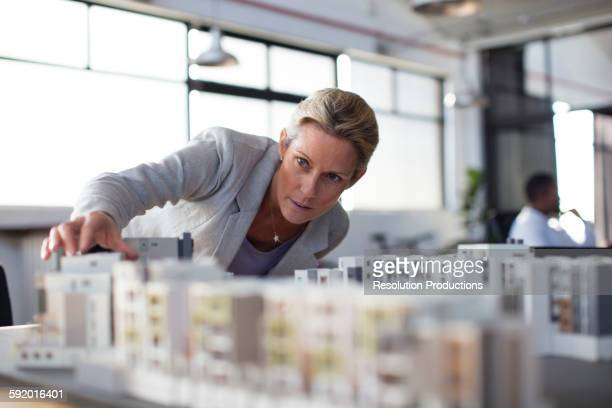 Caucasian architect examining architectural model in office