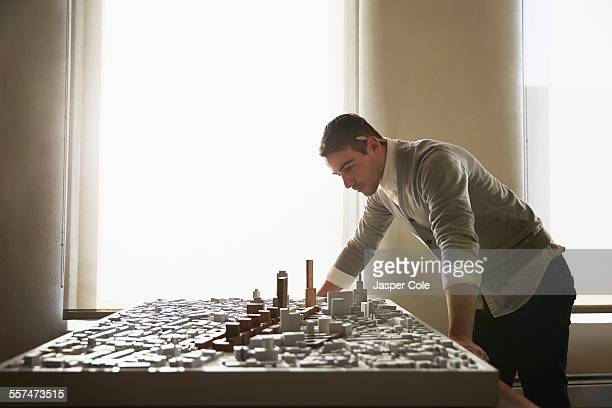 caucasian architect examining urban model in office - model building stock photos and pictures