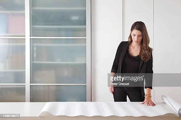 caucasian architect looking at blueprints - 女性建築家 ストックフォトと画像