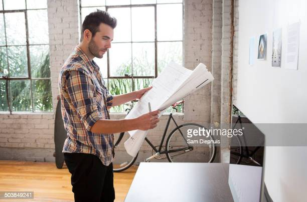 Caucasian architect reading blueprints in office