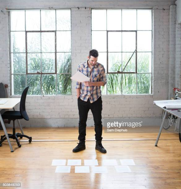 Caucasian architect reading papers in office