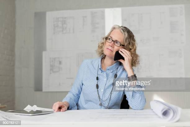 Caucasian architect talking on phone at desk