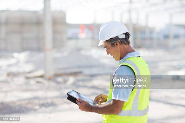 Caucasian architect using digital tablet at construction site
