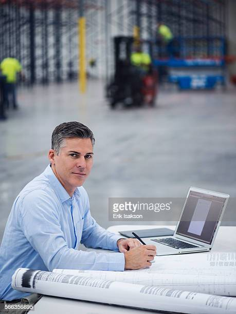 Caucasian architect working in warehouse