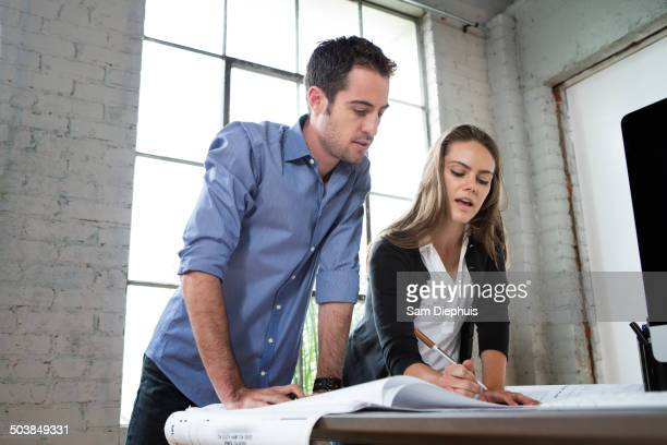 Caucasian architects designing blueprints in office