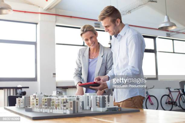 Caucasian architects examining architectural model in office