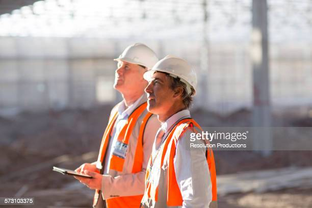 Caucasian architects using digital tablet at construction site