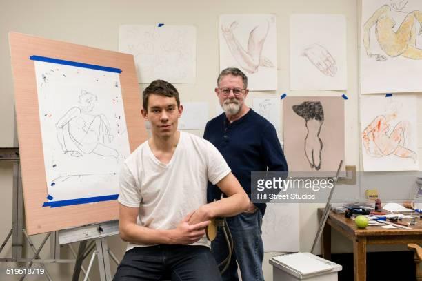 Caucasian artist and student smiling in studio