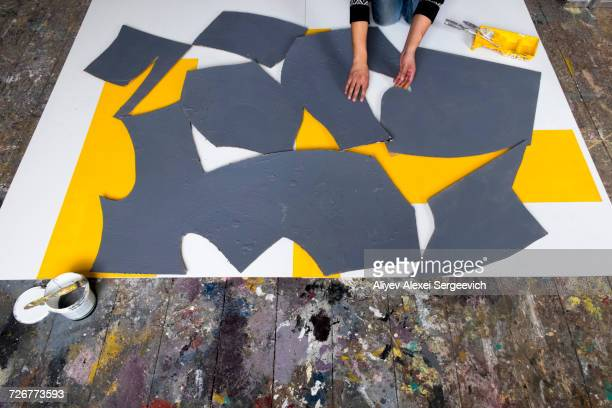 Caucasian artist arranging pieces of painting