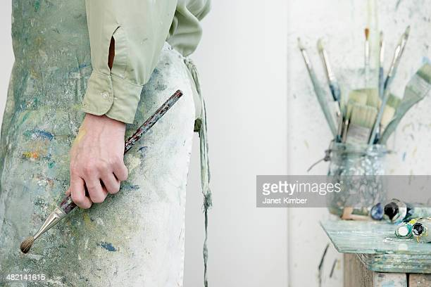 Caucasian artist holding paintbrush in studio