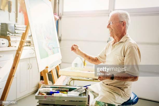 Caucasian artist painting in garage