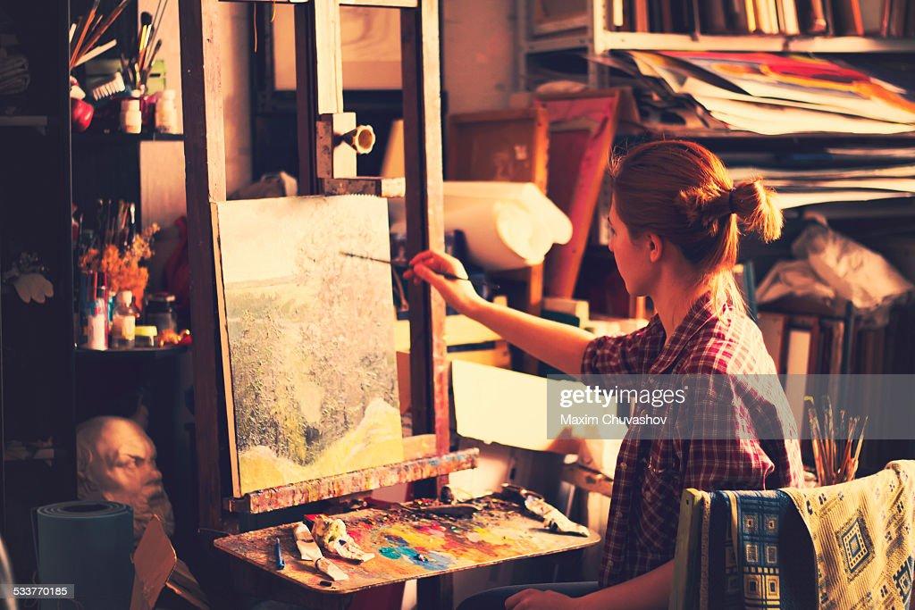 Caucasian artist painting on canvas in studio : Foto stock