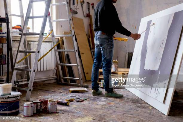 Caucasian artist painting with paint roller