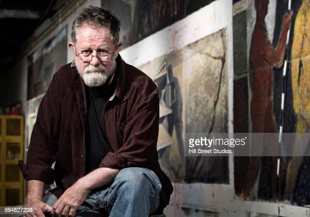 Caucasian artist sitting in studio