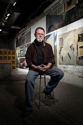 Caucasian artist sitting in studio - gettyimageskorea