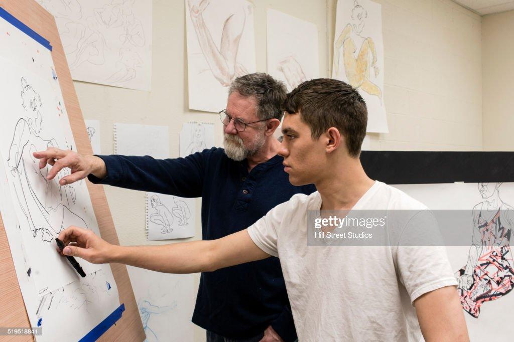 Caucasian artist teaching student in studio : Stock Photo