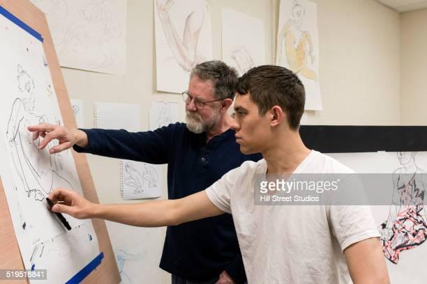 Caucasian artist teaching student in studio