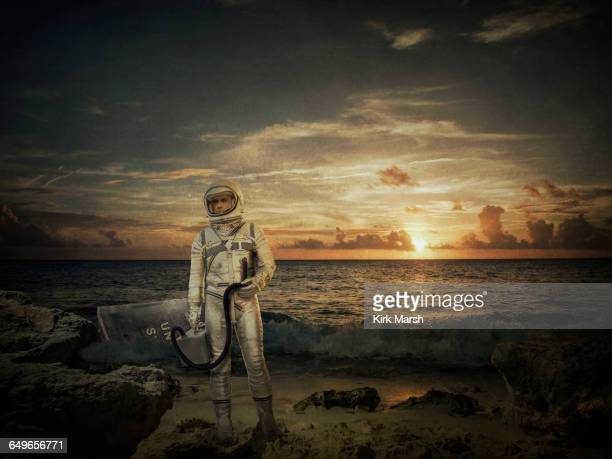 Caucasian astronaut standing on beach at sunset