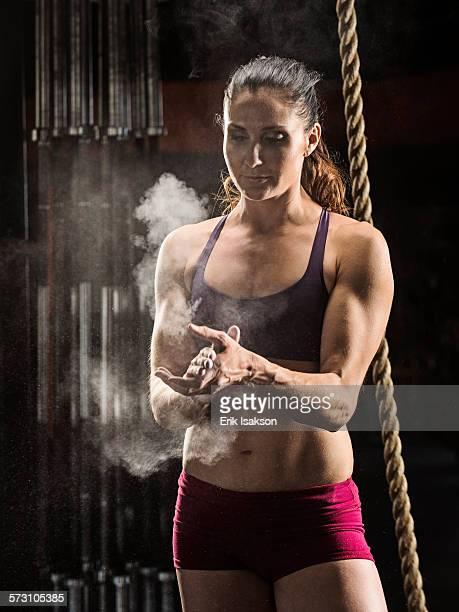 Caucasian athlete chalking her hands in gym