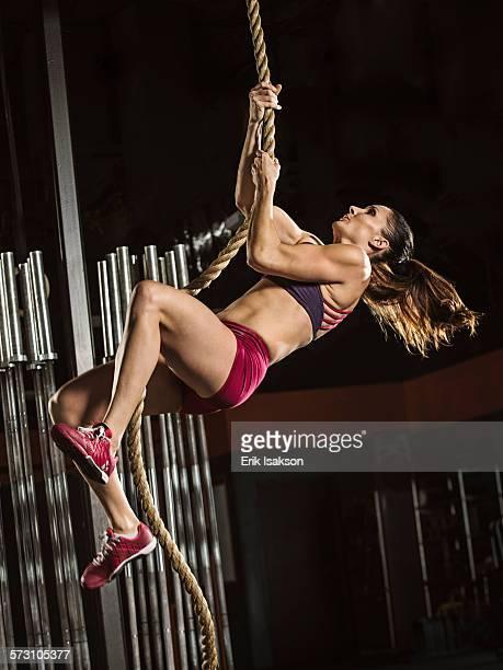 Caucasian athlete climbing rope in gym