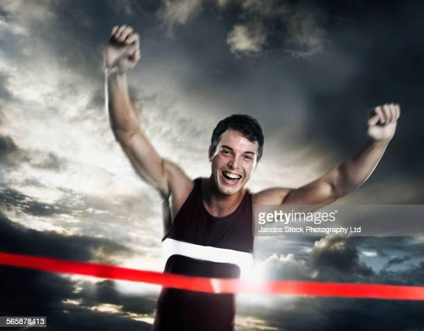 Caucasian athlete crossing finish line in race