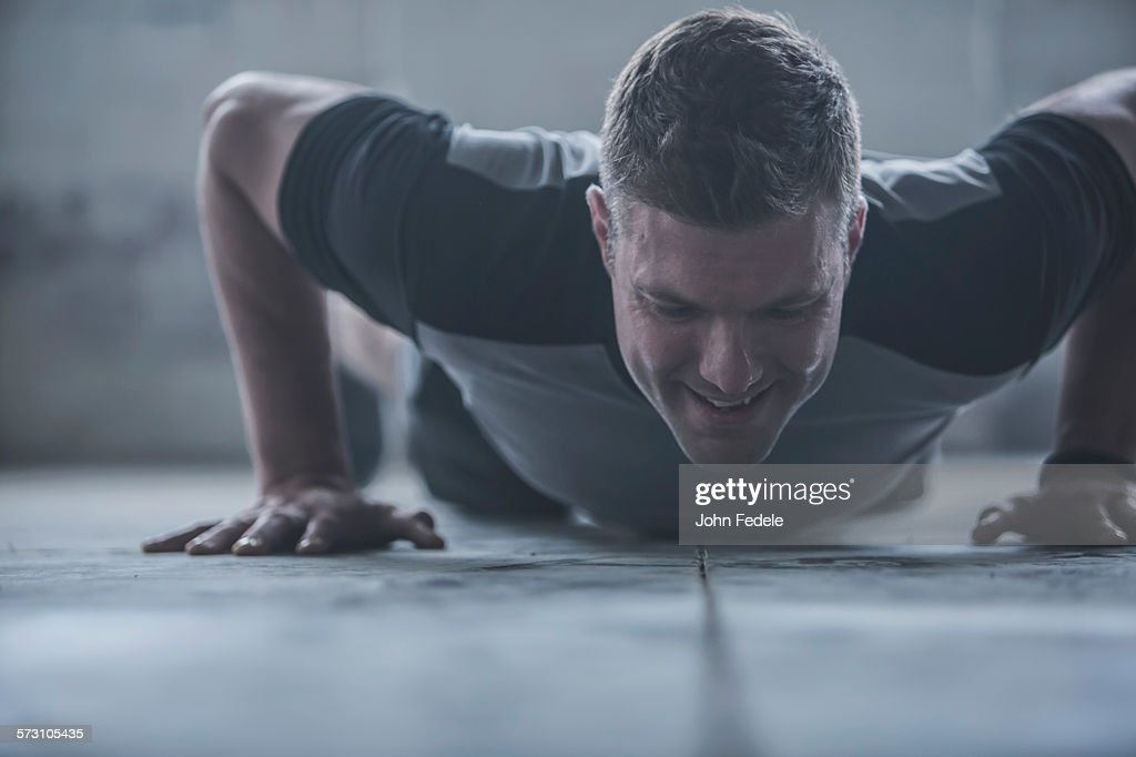 Caucasian athlete doing push-ups on floor : Stock Photo
