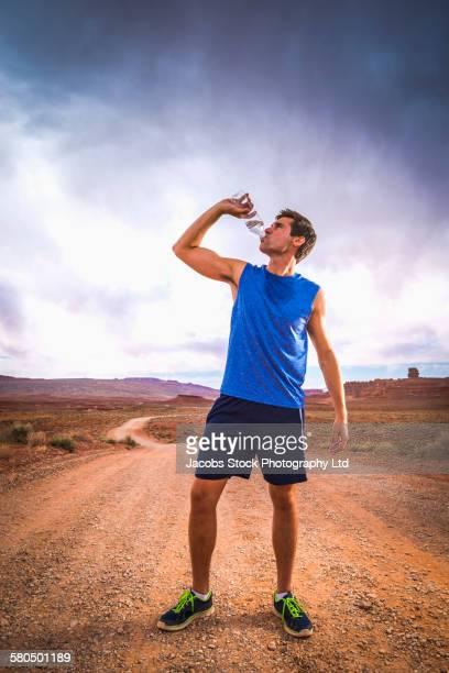 Caucasian athlete drinking water bottle in desert landscape