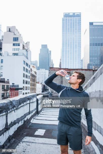 Caucasian athlete drinking water bottle on urban rooftop