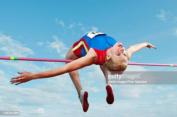 Caucasian athlete jumping over bar