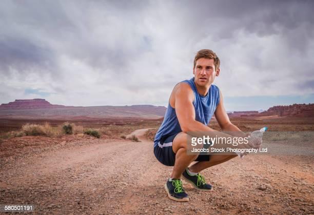 Caucasian athlete resting in desert landscape