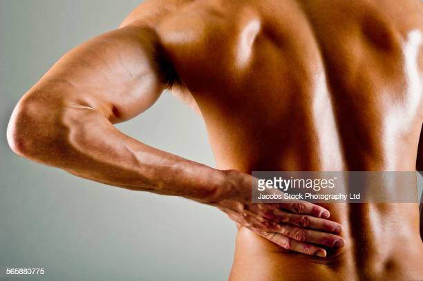 Caucasian athlete rubbing painful back muscles