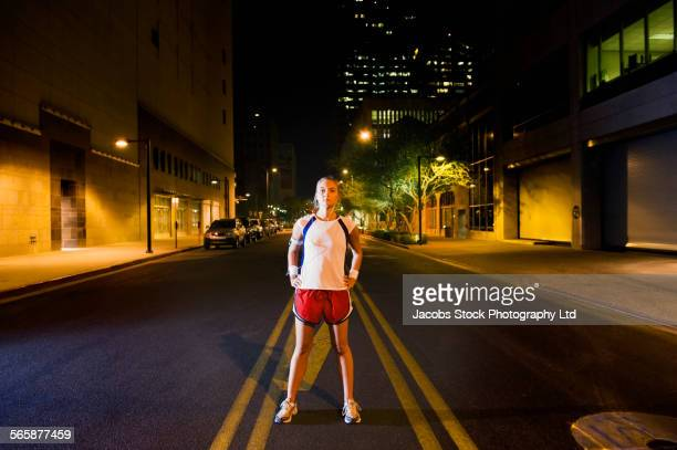 Caucasian athlete standing on street in city at night