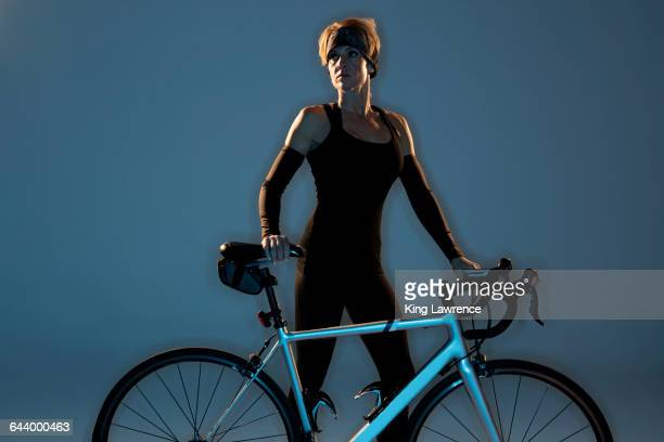 Caucasian athlete standing with bicycle
