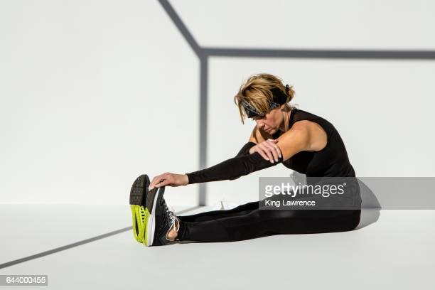 Caucasian athlete stretching leg