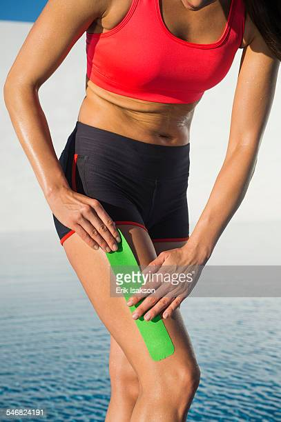 Caucasian athlete taping thigh near swimming pool