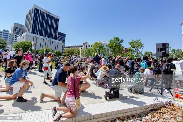 Caucasian attendees kneel and pray in support of AfricanAmericans during the City Collective Prayer March from Norfolk City Hall to Town Point Park...