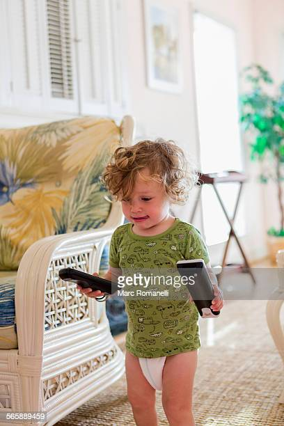 Caucasian baby boy carrying remote controls in living room