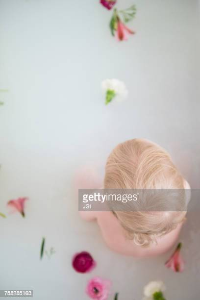 Caucasian baby boy in milk bath with flowers