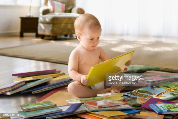 Caucasian baby boy looking at books