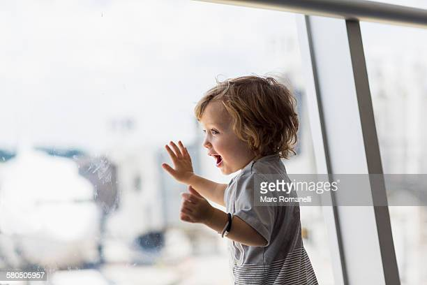 Caucasian baby boy looking out airport window