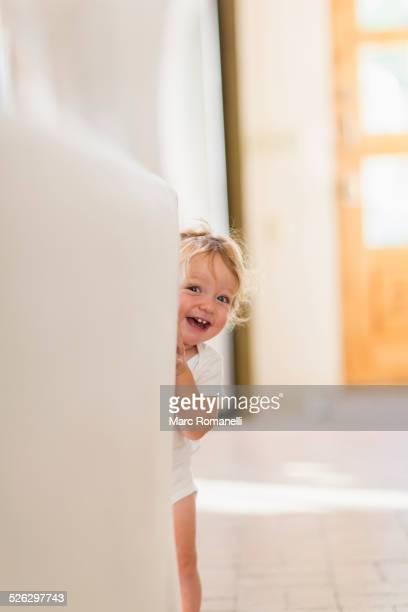 Caucasian baby boy playing hide and seek