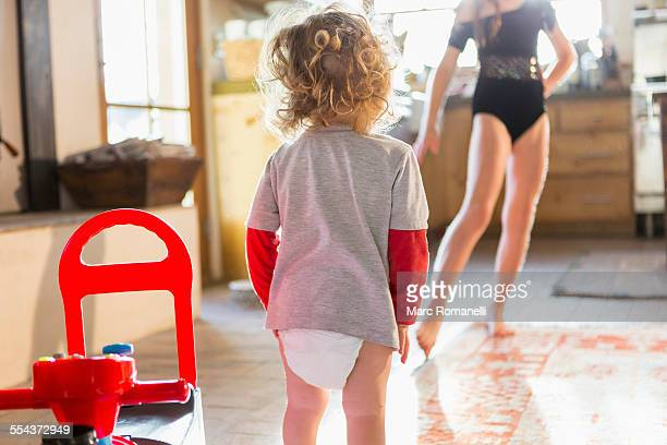 caucasian baby boy playing with older sister in kitchen - diaper kids stock pictures, royalty-free photos & images