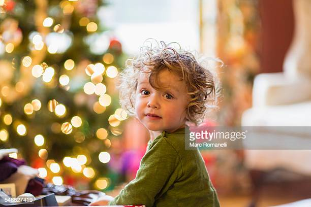 Caucasian baby boy sitting near Christmas tree