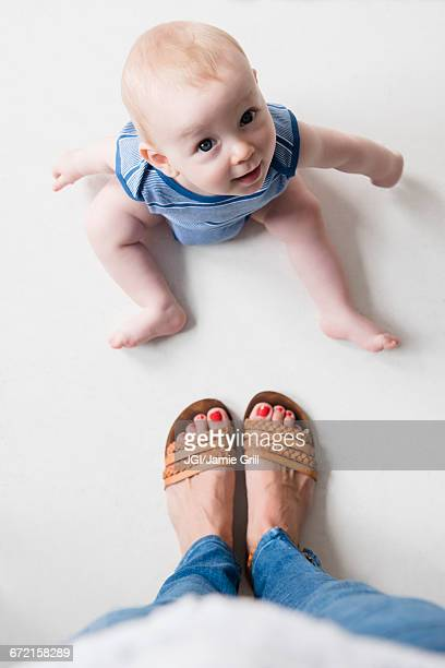 Caucasian baby boy sitting on floor at feet of mother