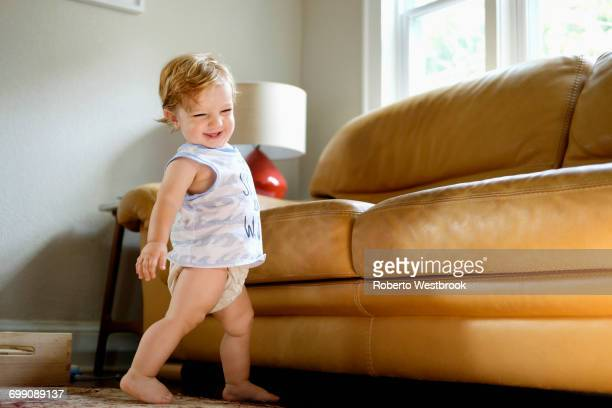 caucasian baby boy walking near sofa - diaper boy stock photos and pictures
