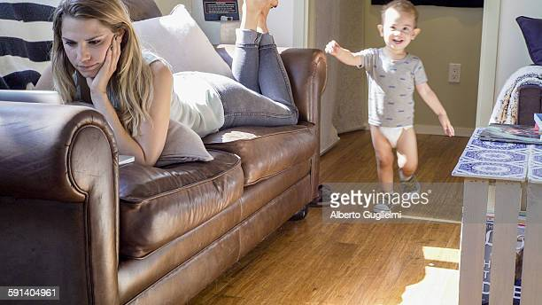 caucasian baby boy walking past mother on sofa - ignoring stock pictures, royalty-free photos & images