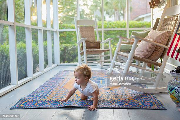 Caucasian baby crawling on porch