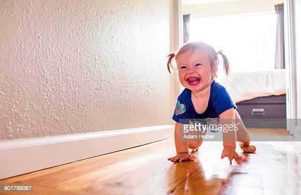 Caucasian baby girl crawling in hallway