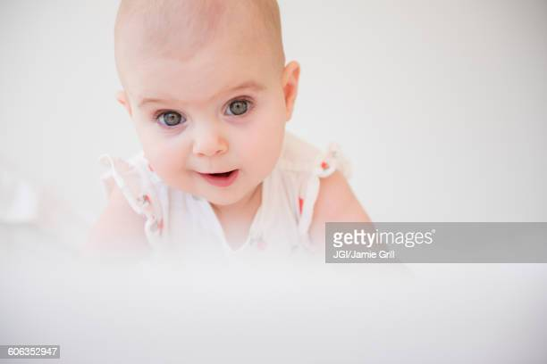 Caucasian baby girl crawling on bed