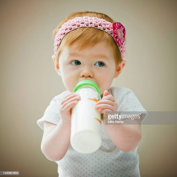 Caucasian baby girl drinking bottle